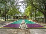 View larger image of Shuffleboard courts under shade trees at WILLISTON CROSSINGS RV RESORT image #2