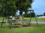 View larger image of 2 swinging benches on lawn in front of trees at KOC KAMPGROUND image #5