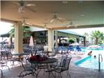 View larger image of Swimming pool with outdoor seating at CAJUN PALMS RV RESORT image #8