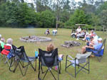 View larger image of Campers sitting around fire pit at AZALEA ACRES RV PARK image #7