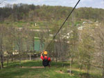 View larger image of Man sliding down rope at WOODS TALL TIMBER RESORT image #12