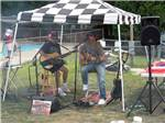 View larger image of People next to their RV sitting at picnic table in the shade at CIRCLE CG FARM CAMPGROUND image #7