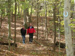 View larger image of Man in red coat and woman in black coat walking along a trail in the woods at BULL RUN REGIONAL PARK image #11