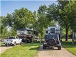 View larger image of Large RVs in large gravel sites with grass and small trees on either side at CHRIS CAMP  RV PARK image #7