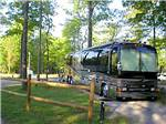 View larger image of Class A motorhome on gravel site with picnic table surrounded by tall trees at ELIZABETHTOWN CROSSROADS CAMPGROUND image #1