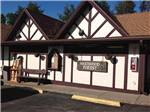 View larger image of General Store with a bench and firewood in front at SHERWOOD FOREST CAMPING  RV PARK image #3