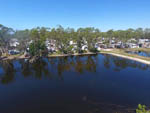 View larger image of An aerial view of the lake and camping sites at WOODSMOKE CAMPING RESORT image #10