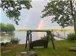 View larger image of Sunset reflected on the lake through trees at LAKE PEMAQUID CAMPGROUND image #1