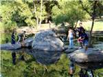 View larger image of People standing on rocks fishing at DRUMMER BOY CAMPING RESORT image #2