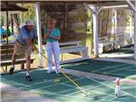 View larger image of Couple playing shuffleboard at RAMBLERS REST RV CAMPGROUND image #2
