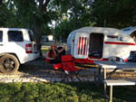 View larger image of Women seated by small trailer raising her glass at THE PARKWAY RV RESORT  CAMPGROUND image #2