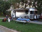 View larger image of Airstream with a man and dog by a fire pit at THE PARKWAY RV RESORT  CAMPGROUND image #3