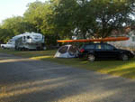 View larger image of Tent site and a car with a kayak on the roof at THE PARKWAY RV RESORT  CAMPGROUND image #4