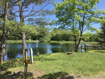 View larger image of Lake view with wooden tables at COOPERSTOWN SHADOW BROOK CAMPGROUND image #4