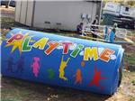View larger image of A large blue pipe with Playtime painted on it in the playground area at EUGENE KAMPING WORLD RV PARK image #6