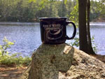 View larger image of Park branded coffee mug sitting on a large rock with view of lake in the background at ACRES OF WILDLIFE CAMPGROUND image #4