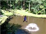 View larger image of Man zip lining over a fountain in the lake  at WILD ACRES RV RESORT  CAMPGROUND image #1