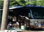 View larger image of A class A motorhome parked under a tree at LAKE GEORGE RIVERVIEW CAMPGROUND image #5