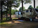 View larger image of A fifth wheel travel trailer parked under trees at LAKE GEORGE RIVERVIEW CAMPGROUND image #7