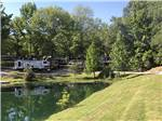 View larger image of Pond surrounded by grass and trees at NORTHERN KY RV PARK image #1