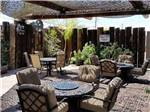 View larger image of Patio area with brown tables and chairs at HITCHIN POST RV PARK image #3
