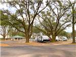 View larger image of RV sites surrounded by trees at I-10 KAMPGROUND image #7