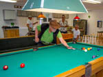 View larger image of People playing pool in the clubhouse at CARAVAN OASIS RV RESORT image #9
