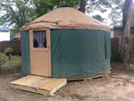 View larger image of Exterior of green and tan yurt on gravel at POMONA RV PARK image #5