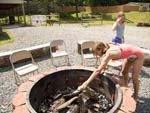 View larger image of A girl playing in the fire pit at COZY CREEK FAMILY CAMPGROUND image #7