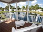 View larger image of Peaceful patio area with white wicker chairs overlooking small pond at SUN-N-FUN RV RESORT image #5