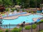 View larger image of Large family community pool with neighboring splash pad at PINE ACRES FAMILY CAMPING RESORT image #7