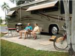 View larger image of Couple sitting next to their Class A motohome camping at DUNEDIN RV RESORT image #3