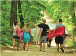 View larger image of A family walking through the trail leading to waterpark at PLYMOUTH ROCK CAMPING RESORT image #5