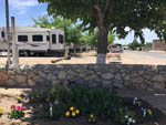 View larger image of RVs behind flower bed with stone wall at MISSION RV PARK image #11