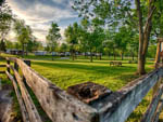View larger image of Rustic wooden fence lines a grassy tree lined picnic area at MILTON HEIGHTS CAMPGROUND image #8