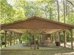 View larger image of Large towable trailer with slideouts parked among tall trees at KETTLE CAMPGROUND CABINS  RV PARK image #4
