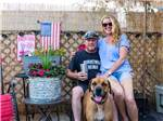 View larger image of A couple sitting with their dog at CIRCLE RV RESORT - SUNLAND image #5