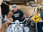 View larger image of A man sitting on a motorcycle with a big dog licking his face at CIRCLE RV RESORT - SUNLAND image #6