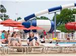 View larger image of Ladies sunbathing with water slides in the background at BETHPAGE CAMP-RESORT image #5