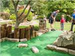 View larger image of A family playing miniature golf at LAKE IN WOOD RESORT image #8