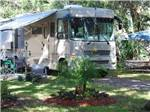 View larger image of Tan RV with awning extended alongside outdoor chairs at VERO BEACH KAMP image #8