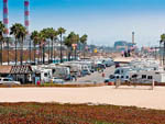 View larger image of Many RVs and Trailers with industrial architecture in background at DOCKWEILER RV PARK image #2