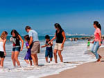 View larger image of Campers playing in the ocean at DOCKWEILER RV PARK image #3