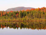 View larger image of Trees with fall colors reflected on the lake at MOUNTAIN LAKE CAMPING RESORT image #1