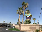 View larger image of Colorful front entry sign with palm trees adorning it at SHANGRI-LA RV RESORT image #2