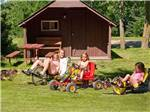 View larger image of Children riding bikes with parent at CAMPARK RESORTS FAMILY CAMPING  RV RESORT image #9