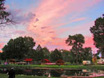 View larger image of Pink sunset behind row of cabins on the water at SPRING CREEK CAMPGROUND  TROUT RANCH image #4