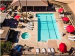View larger image of Aerial view over pool and spa with red umbrellas at RIO BEND RV  GOLF RESORT image #1