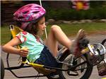 View larger image of A girl with a pink helmet riding a bike at LEDGEVIEW RV PARK image #2