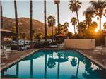 View larger image of The swimming pool area at dusk at OAK CREEK RV RESORT - SUNLAND image #7